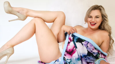 Phoenix lying back, leaning up on one elbow, looking at the camera, tongue in teeth, smiling cheekily, knees bent up, one leg resting on top of opposite knee, holding the side of her floral kimono across her breasts. Phoenix wears silver panties and gold glitter stilettos and has long blonde hair. NZ Pleasures.