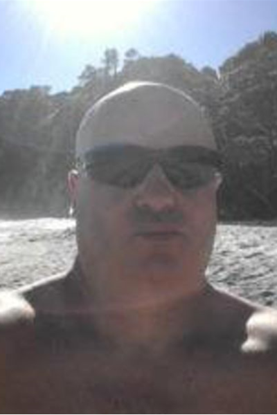 Portrait style photo of Orgasmic Massage with sunglasses on, trees in the background. NZ Pleasures.