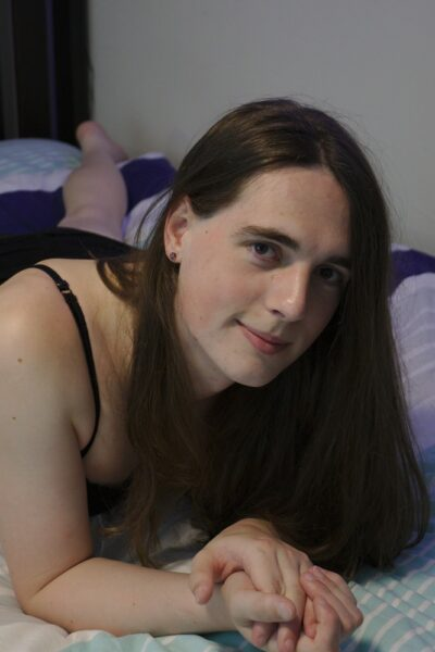 Jade Delenn lying on her bed on her front, leaning up on elbows, head titled to one side. Jade wears a black bra and black mini skirt and has long dark brown hair. NZ Pleasures.