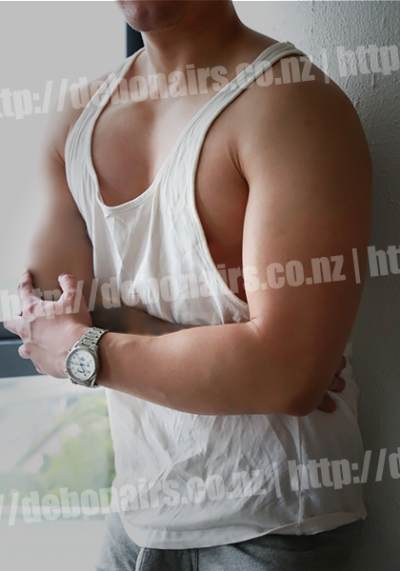 Will standing beside a window, one arm resting on top of the other at chest height. Will wears a white singlet and blue denim jeans. NZ Pleasures.