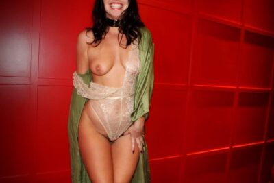 Lilly Idol posing with one leg in front of the other, hand on top of front of bottom of hip, smiling a wide smile. Lilly wears a cream lace bodysuit that has one side down her arm to reveal her breast, a green satin kimono that is undone and also down one arm and has long black hair. NZ Pleasures.
