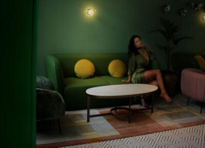 Lilly Idol sitting crossed legged on a green couch in a dark lite lounge, one hand on couch beside her, head titled to one side. Lilly wears a green evening dress and her long hair out. NZ Pleasures.