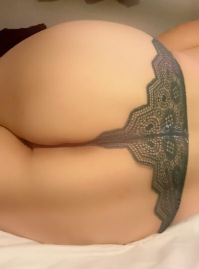 Close up photo of Danielle Deepthroat's buttocks while lying on her side. Danielle wears black lace panties. NZ Pleasures.