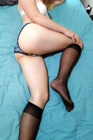 Layla Morgan lying on her side on a bed, one knee bent up, hand on knee. Photo taken from above. Layla wears a white bra, blue floral panties and black knee high stockings. NZ Pleasures.