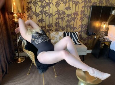 Chloe Beaumont leaning back in a chair, arms over head, legs slightly bent up, resting on a pouf that's in front of her. Chloe wears a black bodysuit, beige stilettos and has long blonde hair. NZ Pleasures.