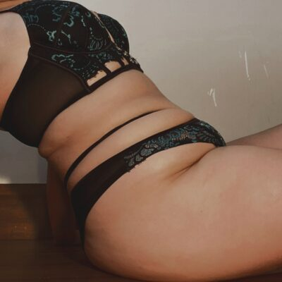 Side on photo of Sienna reclining back on hands behind her. Sienna wears black and green lingerie. NZ Pleasures.