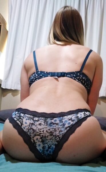 Layla Morgan sitting with back to camera, leaning forward abit, hands on lap. Layla wears blue and white lingerie and has long blonde hair. NZ Pleasures.