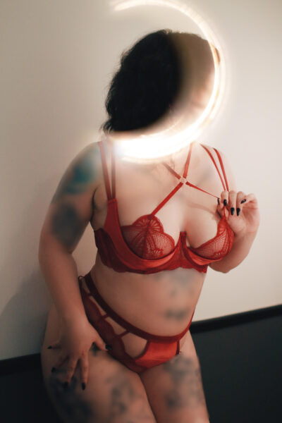 Talia Penmore leaning on her buttocks against a wall behind her, legs together, one hand on side of thigh, the other pulling on the strap of her bra, head turned away from camera. Talia Penmore wears red lingerie, has many tattoos and short black hair. NZ Pleasures.