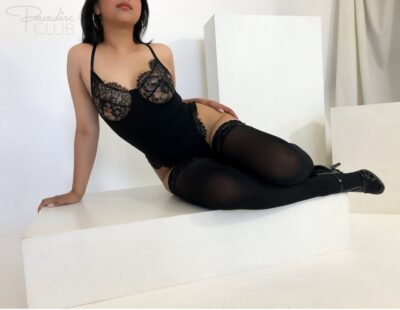 April reclining on one hand, knees bent up, other hand on side of hip. April wears a black bodysuit, black thigh high stockings, black stilettos and has black hair. NZ Pleasures.
