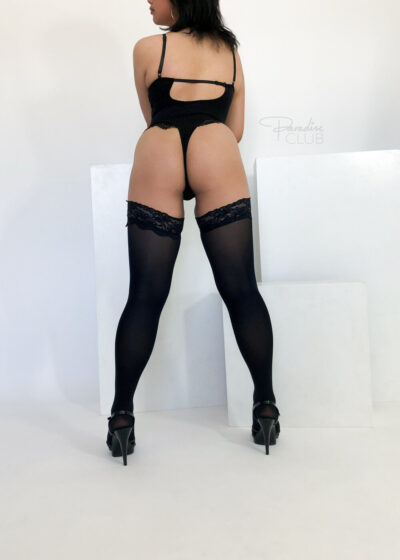 April standing with back to camera, legs wide apart, hands on stool in front of her, head turned to one side. April wears black lingerie, black thigh high stockings, black stilettos and has shoulder length black hair. NZ Pleasures.