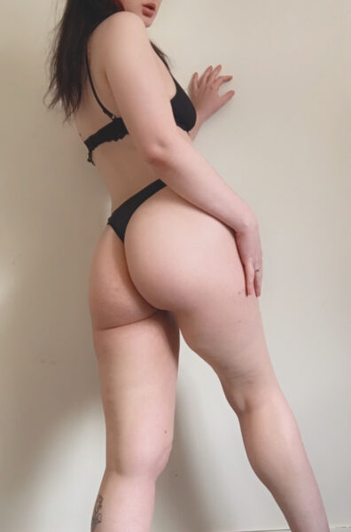 Spencer Ryan posing partially side on to camera, back to camera, legs apart, hand on side of thigh, her other had up on wall, turning around to look at camera. Spencer wears black lingerie and has long black hair. NZ Pleasures.