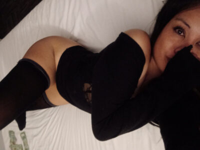 Miss Jade taking a selfie from above, hand covering mouth, back arched, one leg bent up. Miss Jade wears a black bodysuit with long sleeves, black thigh high stockings and has long black hair. NZ Pleasures.