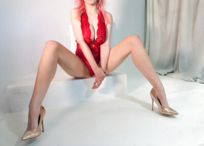 Candy sitting on the edge of a low stool, legs bent, feet wide apart, arms between legs, one hand resting on other hand. Candy wears a red bodysuit, gold heels and has blonde/pink hair. NZ Pleasures.