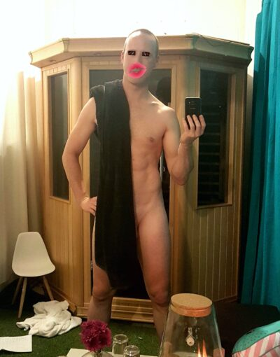 Harley Brixton taking a selfie, posing with legs apart, one hand on hip, naked except for a black towel draped down one side. Cartoon eyes and lips are drawn on his face. NZ Pleasures.