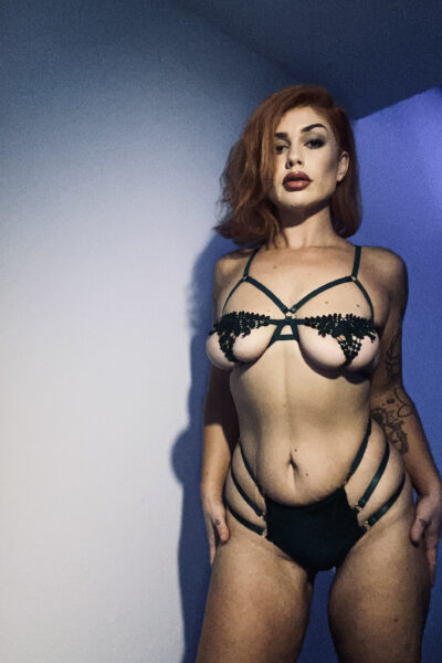 Courtney Lane posing with legs apart, hands on side of hips, looking down at camera. Courtney wears black lingerie and has red hair. NZ Pleasures.