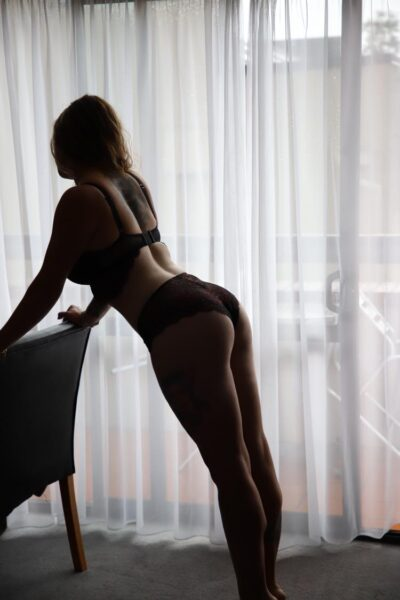 Kali standing behind a chair, leaning forward on hands on back of chair, side on to camera. Kali wears black lingerie and has long brown hair. NZ Pleasures.