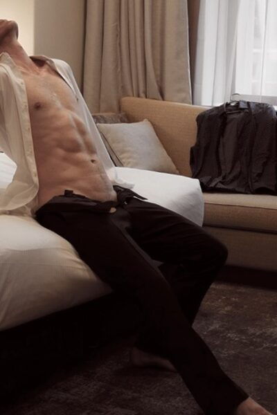 Harley Brixton sitting on the edge of a bed, leaning back on hands either side, head titled back, one leg extended in front of him. Harley wears a white dress shirt that is undone and black pants that are also undone. NZ Pleasures.