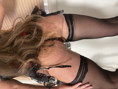 Angelica posing with back to camera, leaning forward slightly, one leg forward, hand on side of thigh, her other arm up on wall beside her. Angelica wears a black corset with suspender belt, black thigh high stockings and has long brown hair. NZ Pleasures.