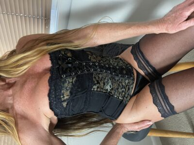 Angelica perching on the front of a chair, one hand on hip, back arched, the other hand on top of thigh. Angelica wears a black and green corset, black panites, black thigh high stockings and has long blonde hair. NZ Pleasures.