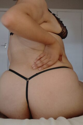 Sienna kneeling, sitting back on feet, back to camera, twisting around towards camera, hand on back of hip. Sienna wears black lingerie with black thong. NZ Pleasures.