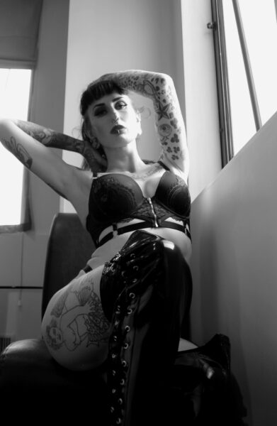 Black and white photo of Pandora Black perching on the front of a chair, one knee bent up, one arm on top of head, the other behind neck. Pandora wears black lingerie, black over the knee boots and has long dark hair and tattoos. NZ Pleasures.