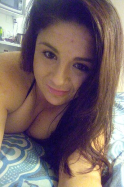 Portrait style selfie of Anna while lying on her front. Anna has long dark brown hair. NZ Pleasures.