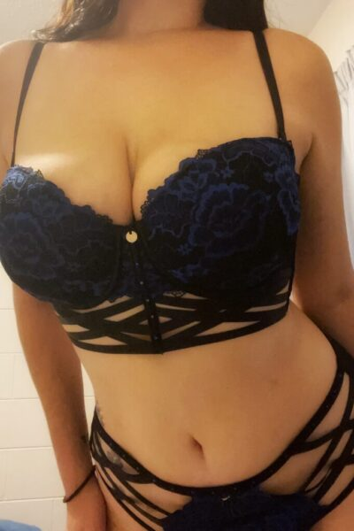Leah Nyx leaning towards the camera, hands either side of thighs. Leah wears black lingerie and has long dark hair. NZ Pleasures.
