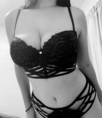 Black and white photo of Leah Nyx leaning towards the camera, hands either side of thighs. Leah wears black lingerie and has long dark hair. NZ Pleasures.