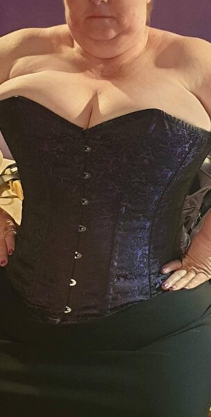 Corrine from mouth to thighs, hands on hips, in a black and purple corset and black mini skirt. NZ Pleasures.