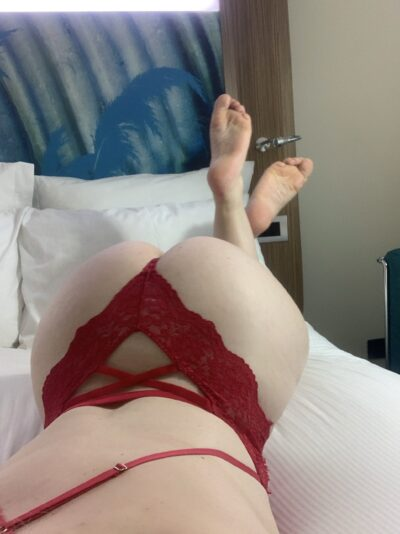 Chloe Beaumont kneeling on hands and knees, taking a photo from over her shoulder, feet in air, crossed at ankles. Chloe wears a red lace bodysuit. NZ Pleasures.
