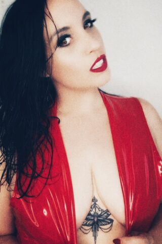 Portrait style photo of Mistress V posing in a red latex top with a low cleavage, her hands holding either side beneath her breasts. Mistress V has long black hair and a tattoo beneath the middle of her breasts. NZ Pleasures.