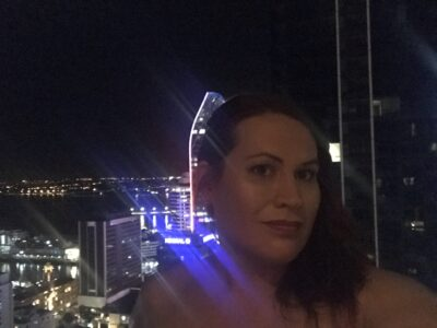 Portrait style photo of Brooklyn posing by a window that looks out over Auckland at night. Brooklyn wears her long hair down one side of shoulder. NZ Pleasures.