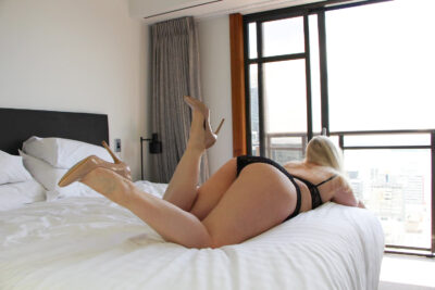 Chloe Beaumont lying on her front on a bed, arms off side of bed, one foot in the air by buttock, the other mid way. Photo is taken partially from behind and to the side. Chloe wears black lingerie and beige stilettos and has long blonde hair. NZ Pleasures.
