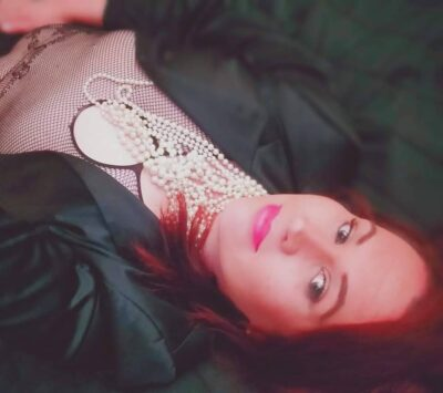 Brooklyn lying on her back looking up at the camera. Brooklyn wears a fishnet stocking top, black jacket that is undone, with lots of pearls around her neck. Brooklyn has red hair. NZ Pleasures.