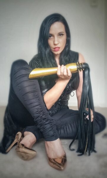Mistress V sitting with one leg crossed under the other, one hand holding the handle of a flogger, her other hand in the long black tassels of the flogger. Mistress V wears a black top, black pants, gold stilettos and has long black hair. NZ Pleasures.