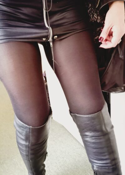 Cropped photo of Mistress Dark Angel from hips to calves. Mistress Dark Angel wears a black pvc mini skirt with a zip up the front, black stockings and silver over the knee leather boots. NZ Pleasures.
