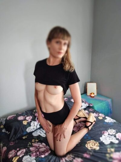 Miss Wilde kneeling on knees on a bed, hands on tops of thighs, looking at the camera. Miss Wilde wears a black t-shirt that is pulled up just above nipples, black short shorts and black wedge heels. Miss Wilde has medium length brown hair. NZ Pleasures.