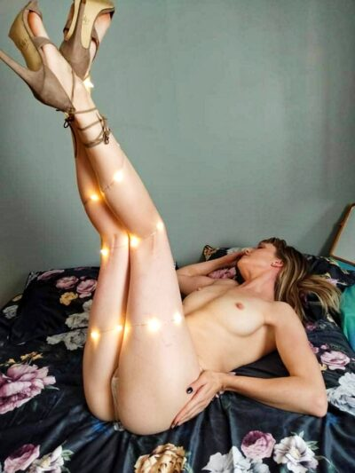 Miss Wilde lying on her back on a bed, legs up in air and crossed at ankles, one hand on side of hip, the other up by her head. Miss Wilde is topless, wears white panties, beige heels and has medium length brown hair and has fairy lights draped over her legs.