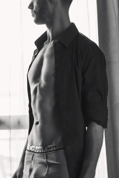 Black and white photo of Christian posing side on to camera, head turned away, arms by sides. Christian wears a dress shirt that is undone and sleeves rolled up to elbows and Calvin Klein boxers. NZ Pleasures.