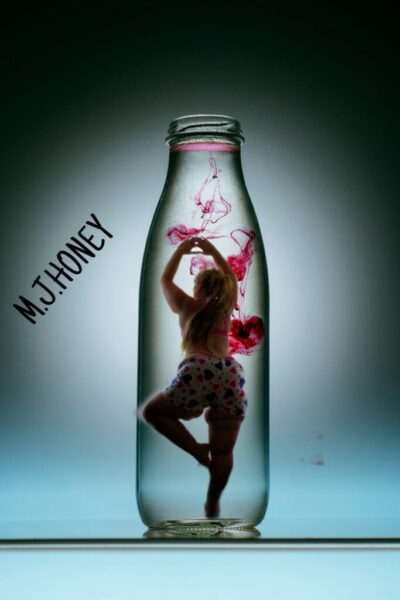 Mary Jane Honey posing with one foot resting upon the opposite leg, hands above head like a ballerina. Posing inside a clear glass bottle. The words M. J. Honey to one side. NZ Pleasures.