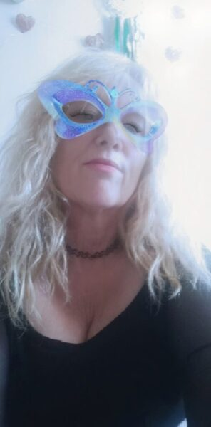 Portrait style photo of Mary Jane Honey with a sticker mask over her eyes. Mary Jane Honey wears a black top and has long blonde hair. NZ Pleasures.