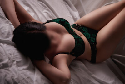 Cassie lying on her back on a bed of white, knees bent up, hands under head which is turned to one side. Cassie wears black with emerald green detail lingerie and has short black hair. NZ Pleasures.