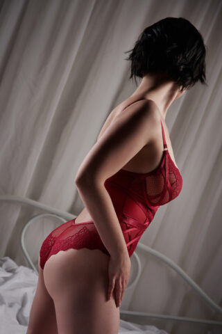 Cassie posing side on to camera, one hand on top of thigh, head turned away from camera. Cassie wears a red bodysuit and has short black hair. NZ Pleasures.