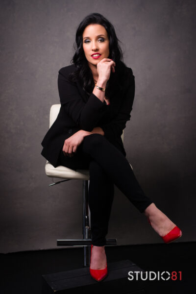 Mistress V sitting cross legged on a white stool, one arm resting on the top of her leg, elbow resting ontop of that arm, hand on chin. Mistress V wears a black suit, red heels and has long black hair. NZ Pleasures.