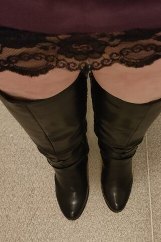 Close up photo of Corrine's legs in black over the knee boots, take from looking down her body. NZ Pleasures.