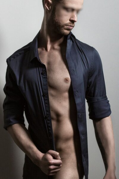 Christian posing naked except for a blue shirt that is undone, sleeves rolled up to elbows, one hand pulling the shirt across his lower regin, head tilted down to one side. NZ Pleasures.