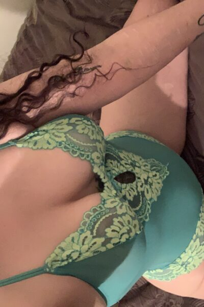 Spencer Ryan taking a selfie from above while kneeling on a bed, knees wide apart, sitting back on heels. Spencer wears a green bodysuit and has long dark hair. NZ Pleasures.