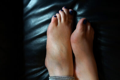 Close up photo of Scarlet Darling's feet, blue toenail polish and a silver anklet on a black leather couch. NZ Pleasures.
