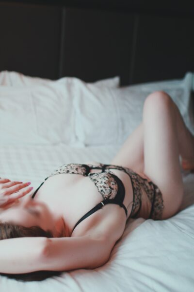 Matilda Watts lying on her back on a bed, one leg bent up, arms above head. Matilda wears black and leopard print lingerie. NZ Pleasures.