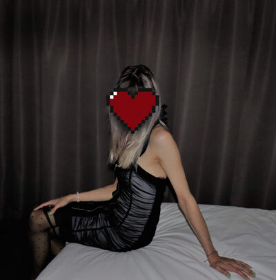 Luna Rune sitting on the side of a bed, legs crossed, leaning on one hand behind her, twisting towards camera, her other hand on top of knee. Luna wears a black sleeveless black dress, black stockings and has long blonde hair. There is a red love heart sticker hiding her face. NZ Pleasures.